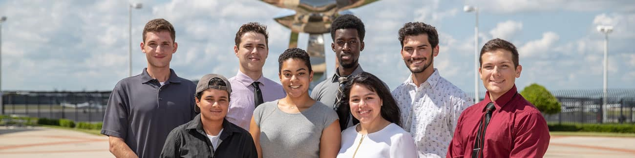 Group of students standing outdoors near a statue at Embry-Riddle Daytona Beach
