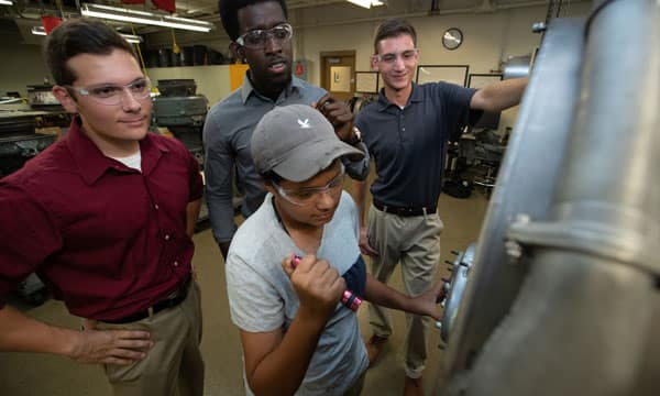 FedEx Purple Runway scholarship recipients working on a jet engine