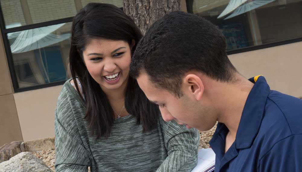 two students laughing and working