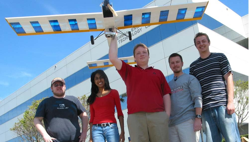 Embry-Riddle students hold a remote-control airplane.
